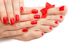 Relaxing Red manicure and pedicure with a bow Stock Photos