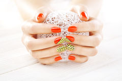 Red manicure with a white ball of yarn Stock Image