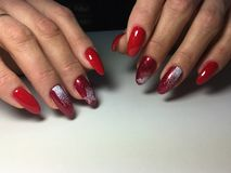 red manicure with white snowflakes on long nails stock photo