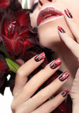 Red manicure with white wavy lines. Royalty Free Stock Photos