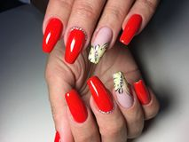 red manicure with a yellow butterfly royalty free stock photos