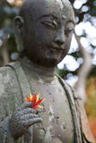 Red maple in hand of image of Buddha in Japan. Stock Photo