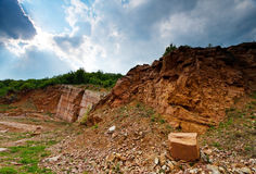 Red marble formation landscape. Red and black marble in an abandoned mine profiled on a stormy sky Stock Photography