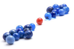 Red marble in the middle of blue marbles Royalty Free Stock Images