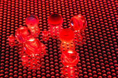 Red marbles on a grid lit in red light. This shot shows some marbles lit with red light Royalty Free Stock Photography