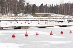 Red marine buoy in frozen water in harbor Stock Photos