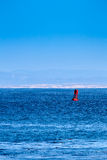 A red marker buoy floating in the ocean. Stock Photography