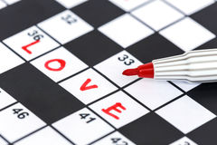 Red marker on Crossword - Love. Close up red marker on Crossword - Love Royalty Free Stock Photography