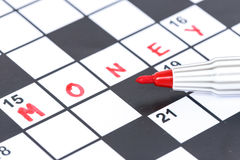 Red marker on Crossword - Money. Close up red marker on Crossword - Money Stock Image