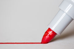 Red marker draws a line. Close up photo stock image
