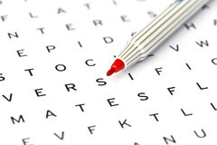 Red Marker on solving crossword puzzle Stock Photo