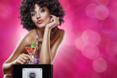 Red martini. Close up portrait of young woman in afro wig on color back Royalty Free Stock Image