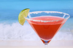 Red Martini cocktail with a lime on the beach. While on vacation Stock Images