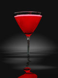 Red martini glass in water. Red cocktail in martini glass in water, black background stock illustration