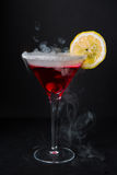 Red martini with lemon. Frosted red martini glass with a slice of lemon. Smoking hot martini Royalty Free Stock Photography