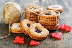 Red marzipan hearts, cookies and ball of twine. Royalty Free Stock Images