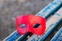 Red mask. Painted red mask lying on blue old bench Royalty Free Stock Photos