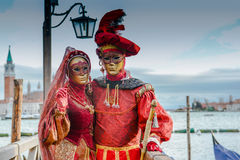 Red masked couple on the pontoon in Venice Stock Photo