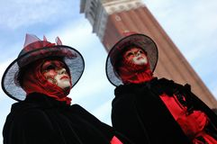 Red masks twins. Two identical masks against a tower and blue sky in Venice Royalty Free Stock Photo