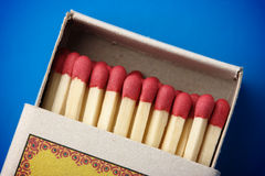 Red matchsticks in the box on blue background Royalty Free Stock Image