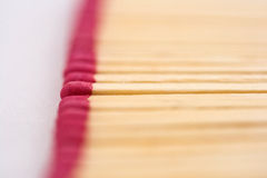 Red mathes. Red wooden matches on white background (focus on one Stock Images