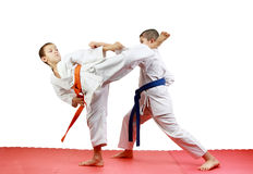On a red mats sportsmen are training paired exercises karate Stock Images