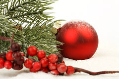 Red matt christmas ball on snow and red rowanberries Royalty Free Stock Image