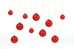 Red matt christmas balls hanging on golden strings on white background Royalty Free Stock Photo