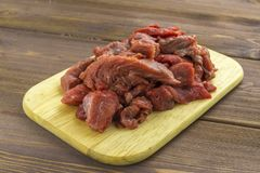 Meat beef cut into pieces lies on a wooden Board stock photos