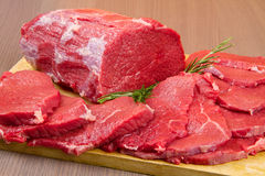 Red meat chunk and steak isolated over wood background Royalty Free Stock Photos
