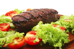 Red meat served on wooden plate with vegetables Stock Photo