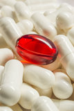 Red medical capsule among white ones macro Royalty Free Stock Photos