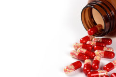 Red medical capsules and bottle isolated Stock Image