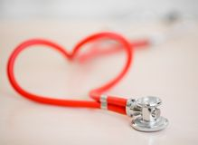 Red medical stethoscope in shape of heart on table Royalty Free Stock Photos