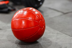 Red medicine weight ball on gym floor closeup Royalty Free Stock Photos