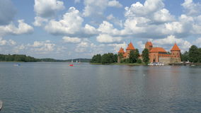 A red medieval castle in Trakai Lithuania GH4 4K UHD. A red in paint color medieval castle in Trakai Lithuania surrounded with a beautiful lake and some people stock footage