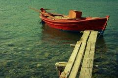 Red Mediterranean fishing boat in the sea . Old Fisherman Boat Stock Photo