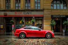 Red Mercedes-Benz Outside a Cafe. A high-performance Mercedes-Benz C63 AMG rests in front of a local cafe in Glasgow, Scotland Royalty Free Stock Photos
