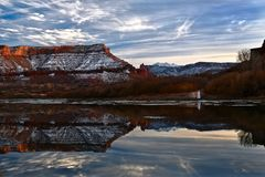Woman with a lamp standing on the river bank with a view of Fisher Towers and La Sal Mountains under snow. Red mesa and its reflection in Colorado River in royalty free stock photography