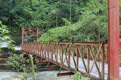 A red metal bridge over a rushing stream during on a cloudy day in the hills of Batatal. Stock Photography