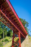 Red metal bridge in the summer. Old red metal bridge in perspective in the summertime Royalty Free Stock Photos