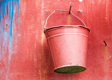 Red metal bucket on the wall Stock Photography