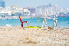 Red metal chair on sandy beach, Montpellier France. Red metal chair on sandy beach sunny day Montpellier France stock images