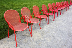 Red Metal Chairs and Green Grass Stock Photos