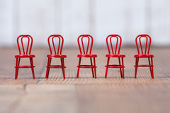 Red metal chairs lined up on wooden floor Royalty Free Stock Photo