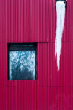 Red metal corrugated wall with window and sausage Stock Photos