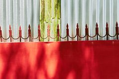 Red metal gate with welded arrows against a silver wall. Design detail of a red metal gate with welded arrows attached to the upper edge, pictured against a wall royalty free stock photo