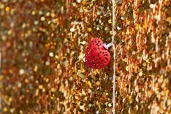 Red metal heart on a golden background. Soft focus. Love and valentine concept. Lots of shining sparkles on a background stock photos