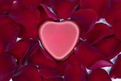 Red metal heart and red rose petals. A shiny red metal heart on a bed of red rose petals stock photos