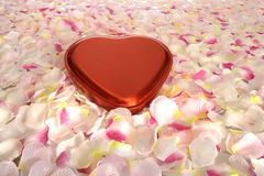 Red metal heart shaped box. Lying between pink flower leafs Stock Photography